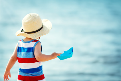 little boy playing at the beach in straw hat